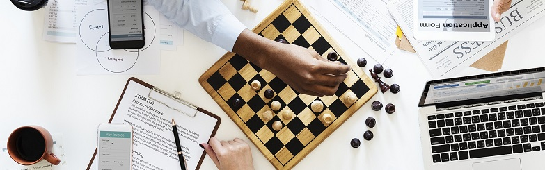 Picture of a game of chess, computer, papers, coffee.